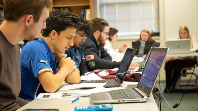 Students study behind laptops in class