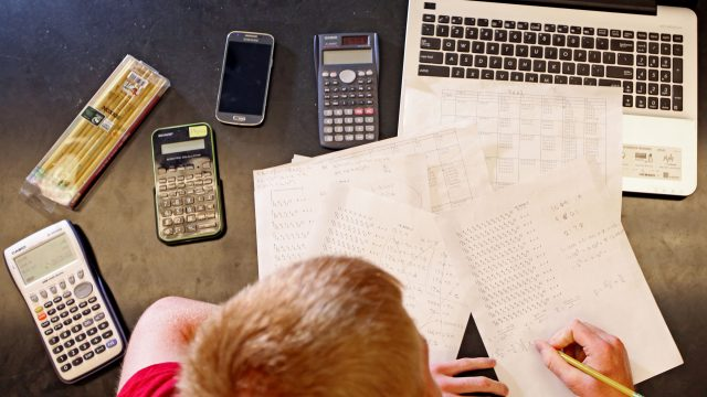 Student study formulas with calculators and laptop