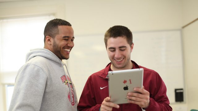 Two male students viewing an iPad