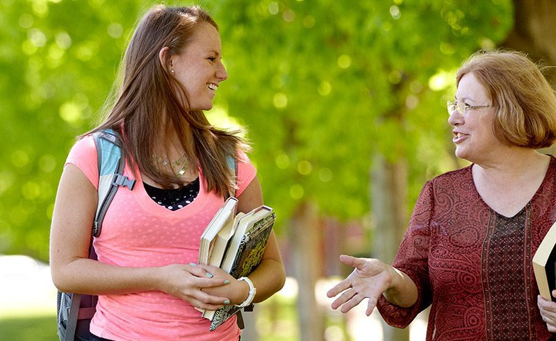 Female student talking to a female professor on the campus mall
