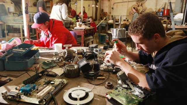 Two male students work with mechanical parts