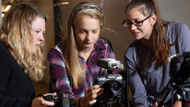 Three female students behind a digital camera