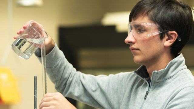 Chemistry student pouring liquid into test tube.