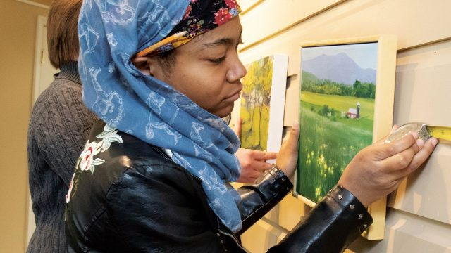 Female student places photo in an art gallery
