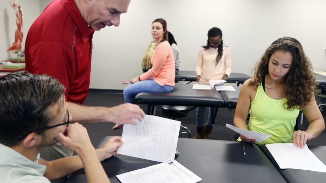 Athletic Training instructor reviews paper with students