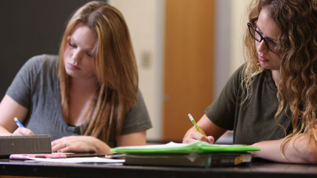 Two female students taking notes