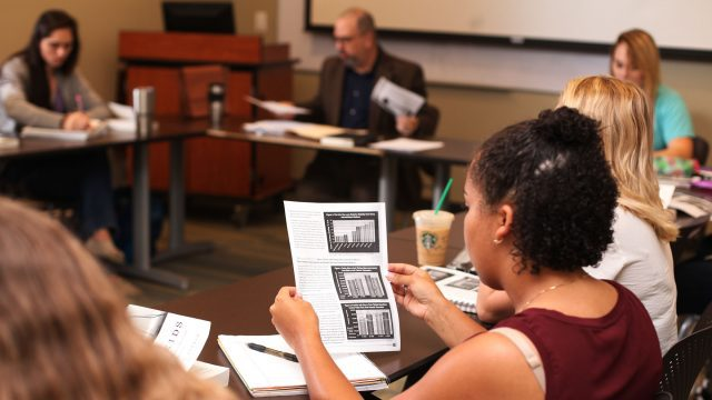Female student reviews a paper in class
