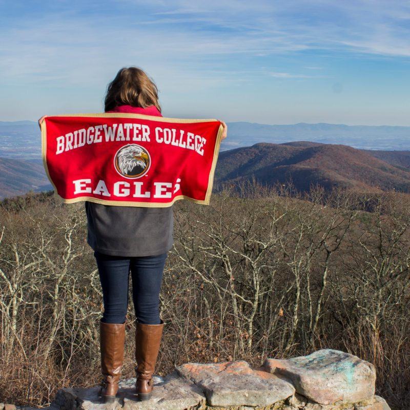 Student at Reddish Knob holding Bridgewater College flag