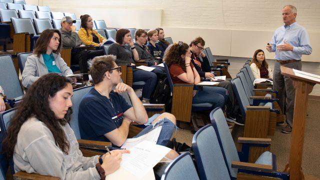 A guest lecturer talks to a Business class