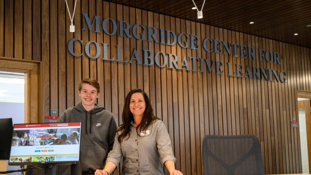 Student and staff member pose behind the Morgridge Center For Collaborative Learning front desk