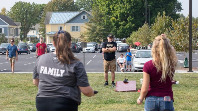 Students and families play cornhole on campus