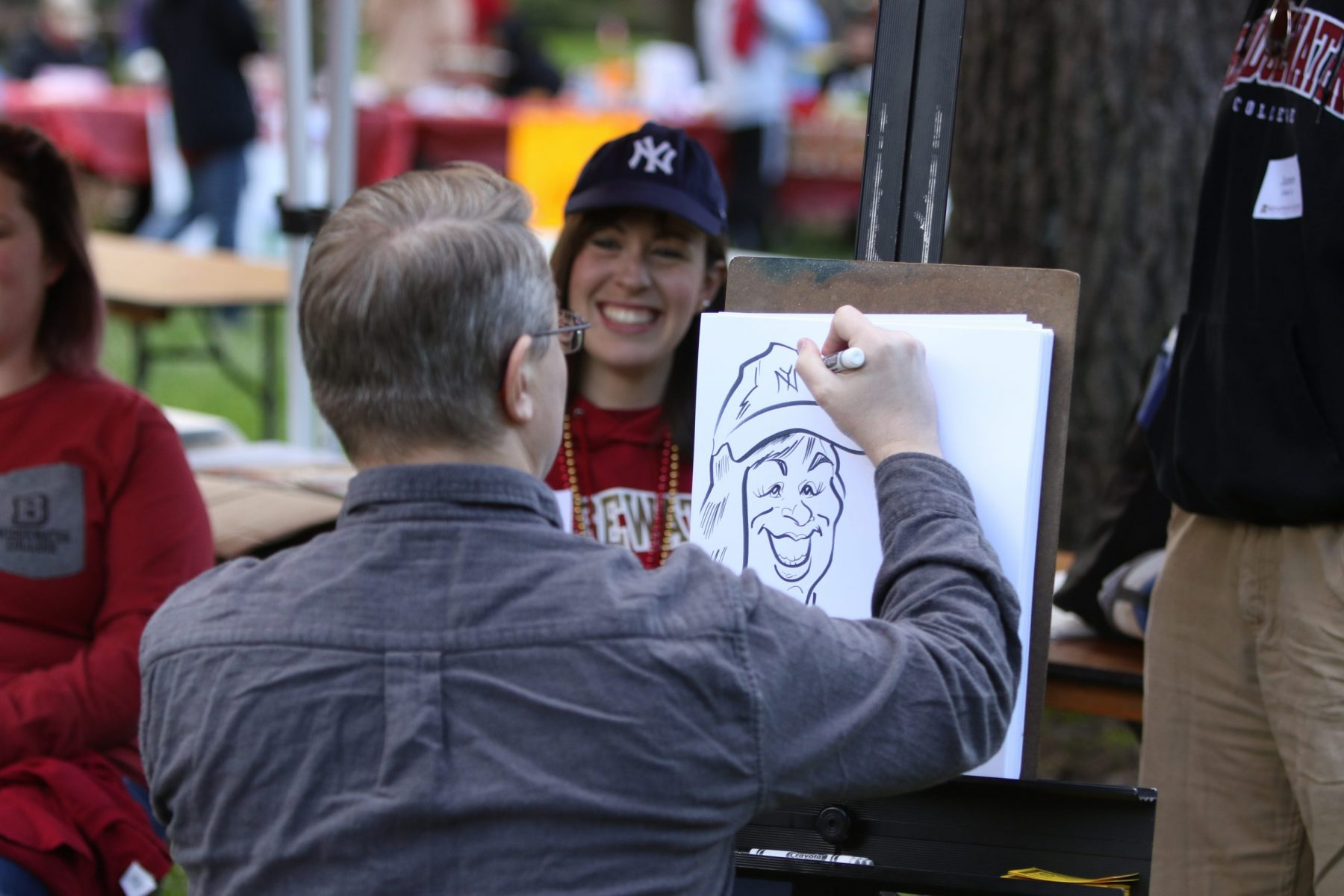 Man sitting down draws photo of woman sitting down