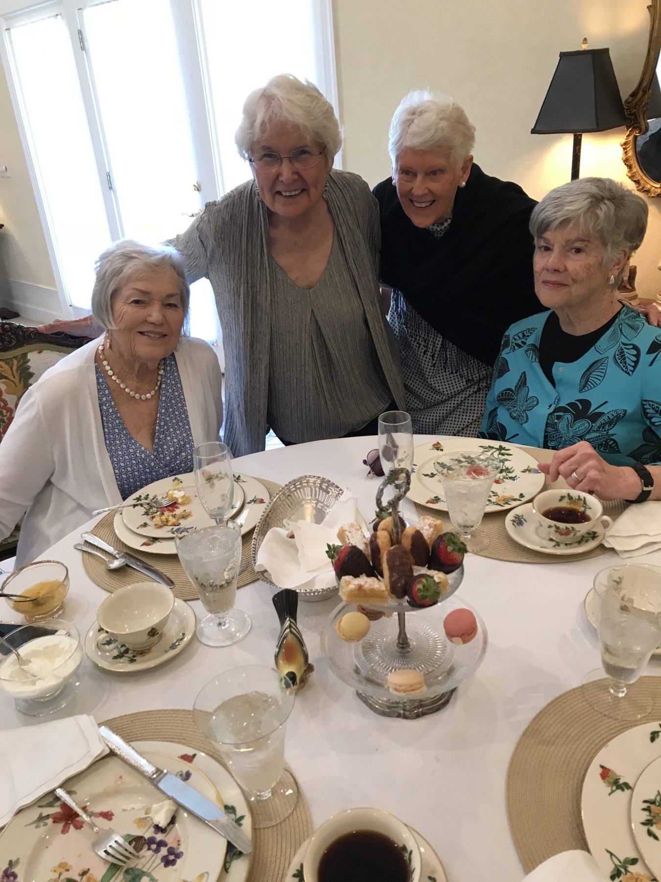Four older women sit around a table