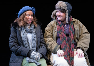 Two people dressed in winter clothing sit on a bench|two people dressed in winter clothing sit on a bench