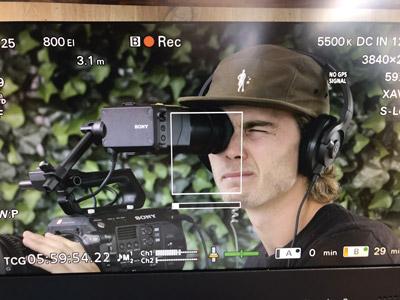 Man looking through a video camera|