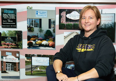  Woman crouches down in front of wall covered in photos