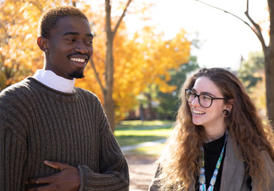 Two students talk to one another on campus|Two students talk to one another on campus