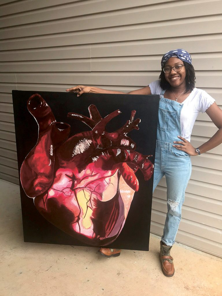 Young woman stands next to a painting of a human heart
