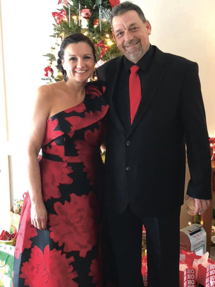 Woman in red dress stands next to man in tux
