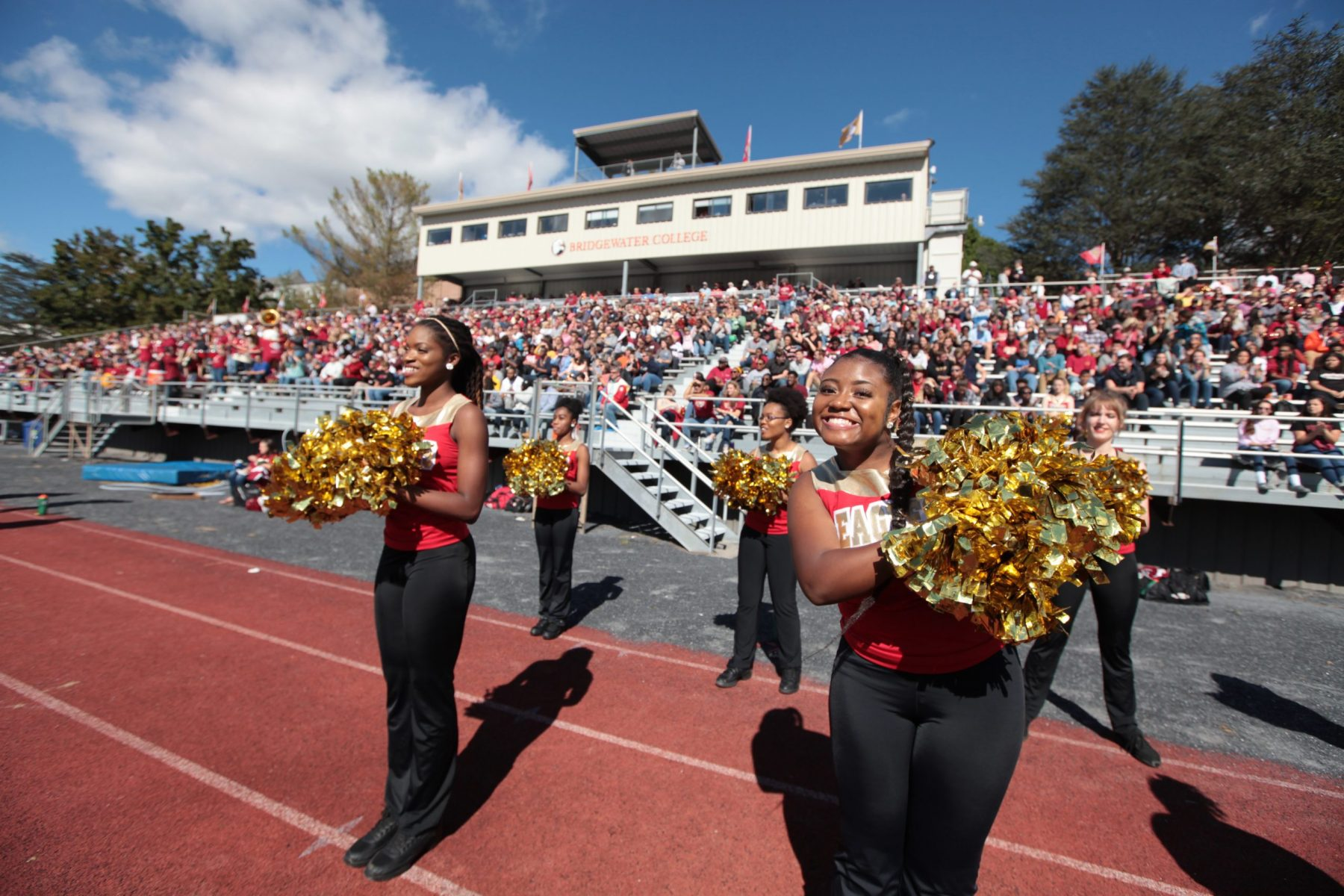 Cheerleaders stand in front of crowded stands