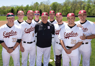 College baseball players stand on either side of their coach on the field||