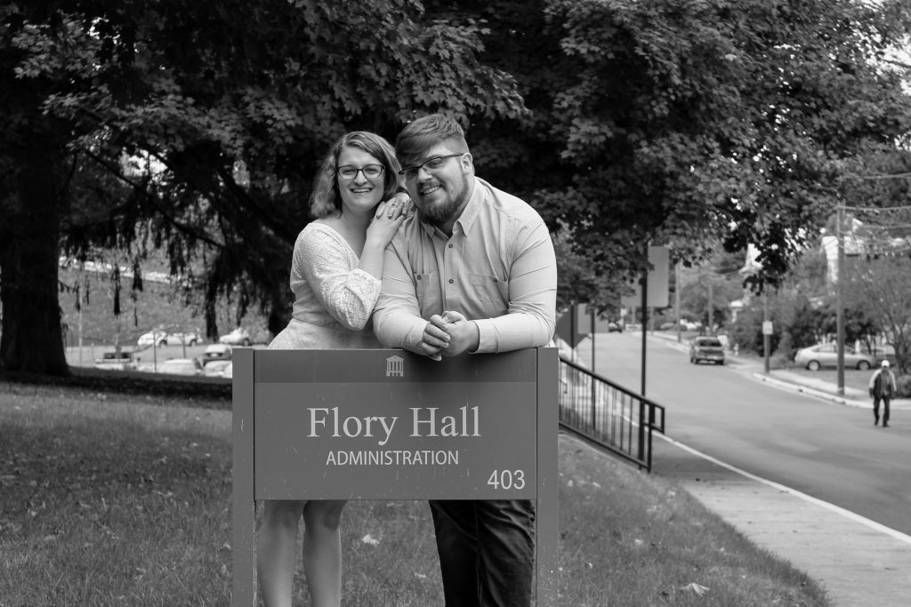 Man and woman stand behind sign that says Flory Hall