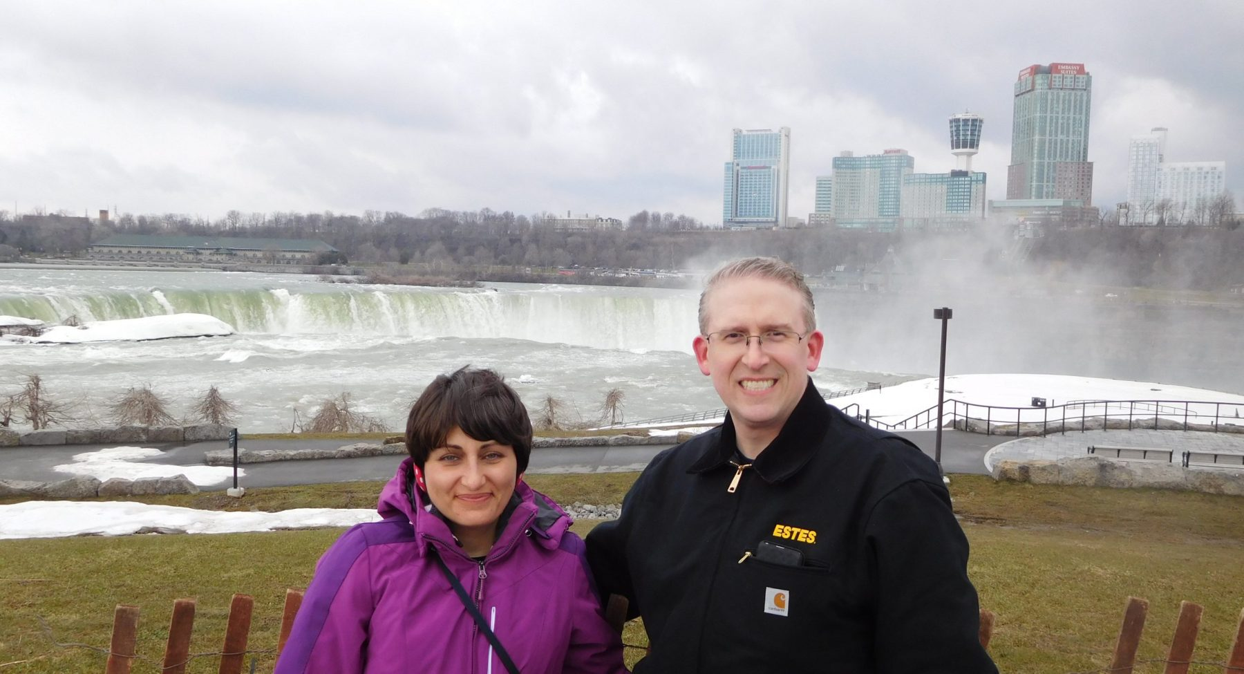 Woman and man stand in front of waterfall with skyline in background