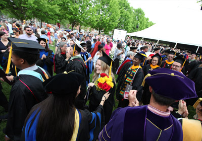 young woman holding flowers wearing a cap and gown in a crows of people||||||||||||||||