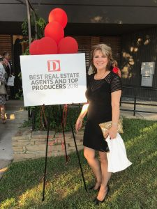 Woman stands next to sign that says Best Real Estate Agents and Top Producers 2018