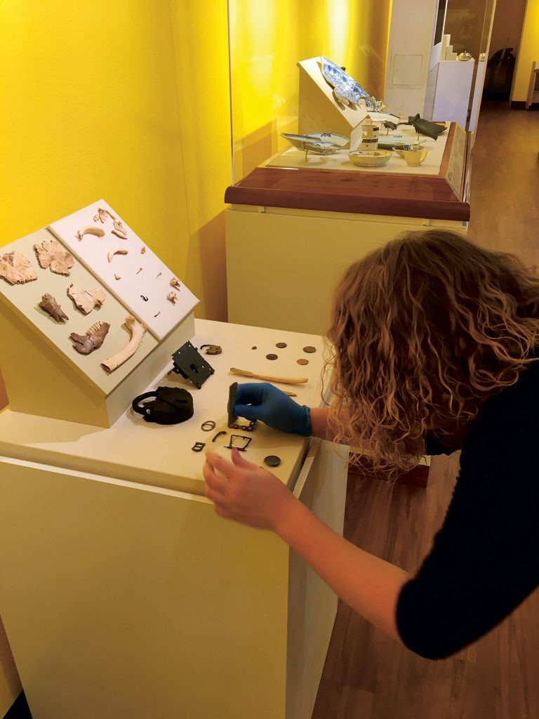 woman brushes artifacts on a display table