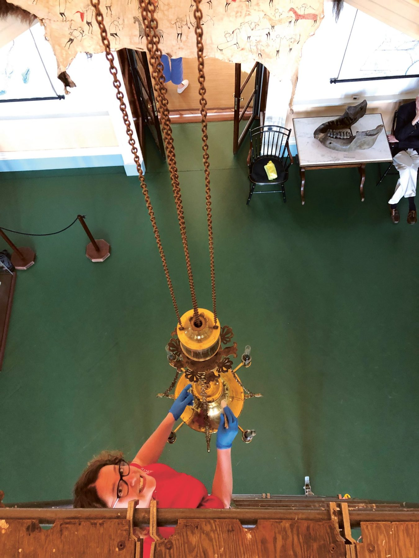 woman cleans a light fixture hanging from the ceiling