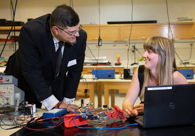 Man in suit stands stands next to student who is seated in front of a computer. A red robtics arm rests on the table between them. Man in suit stands stands next to student who is seated in front of a computer. A red robtics arm rests on the table between them. 