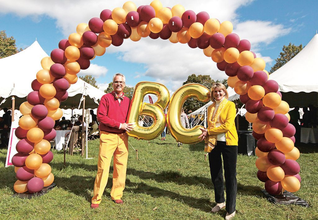two people stand in the middle of an arch made of balloons holding gold B and C balloons