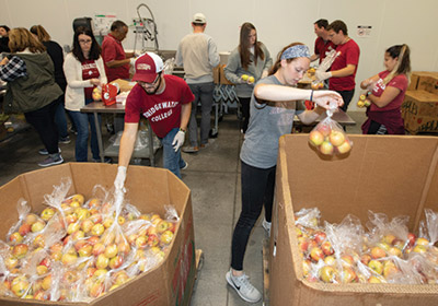 students working at the food bank|students packing boxes with food