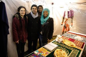 Four students stand in front of a table with food