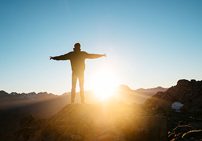 Photo of person facing sunrise with arms spread wide|Photo of person facing sunrise with arms spread wide