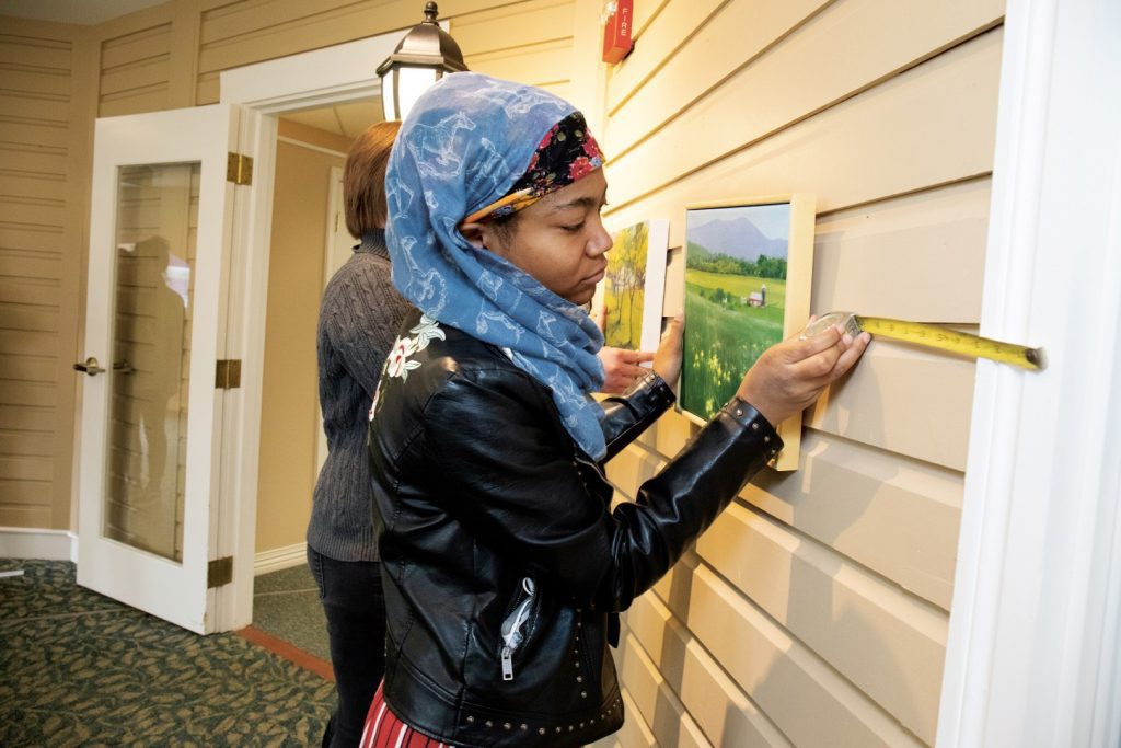 Young woman hangs a painting on a wall with a tape measure