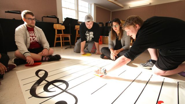 students in a music ed classroom make use of a music staff imprinted rug on the floor
