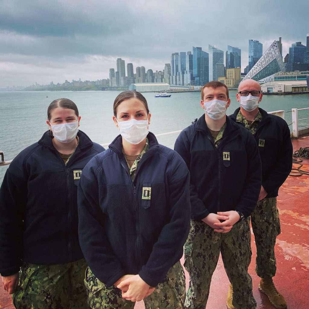 Four people stand on a dock wearing face masks
