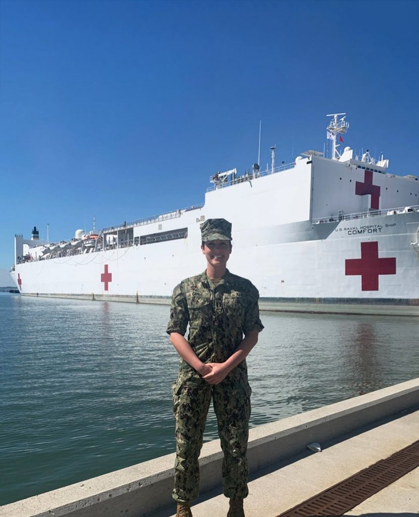 Woman in Navy fatigues stands in front of U.S. Naval hospital ship Comfort