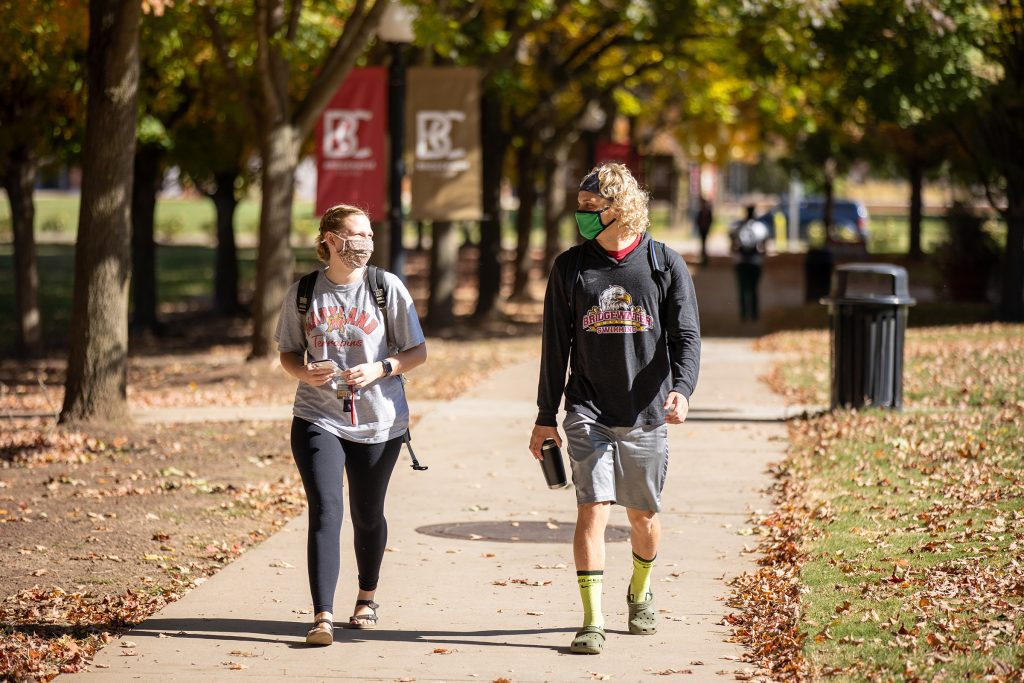 A female and male student walk on Bridewater's campus wearing masks
