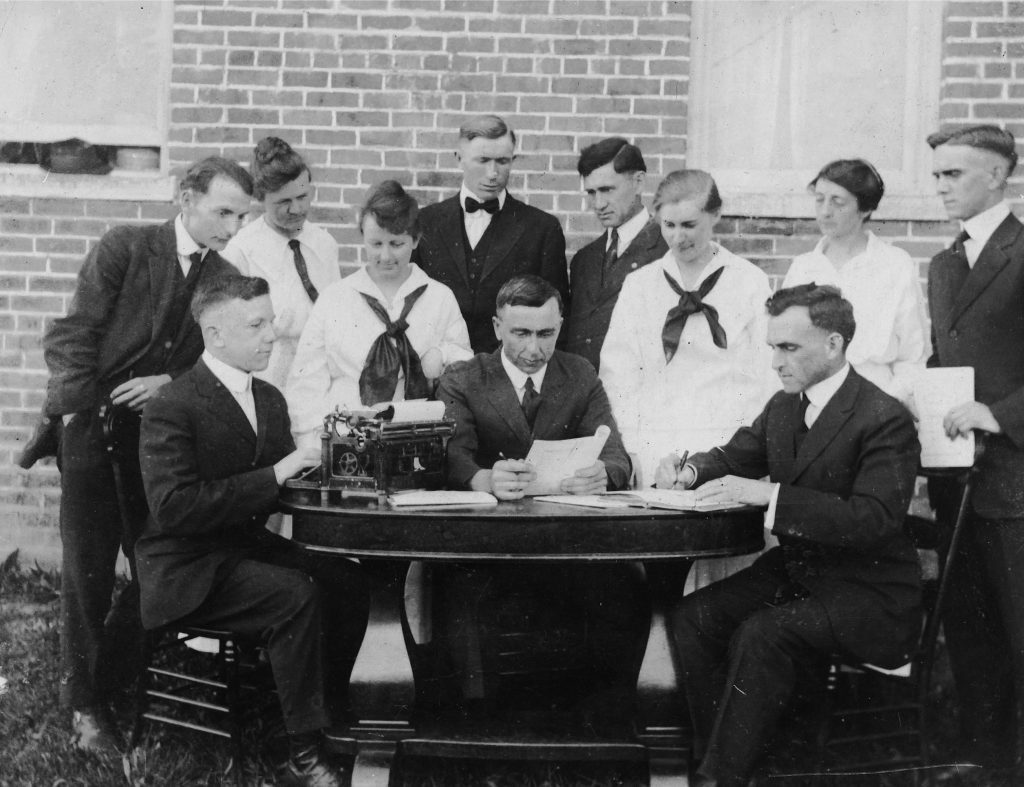 group of people sit around a table with a typewriter and papers