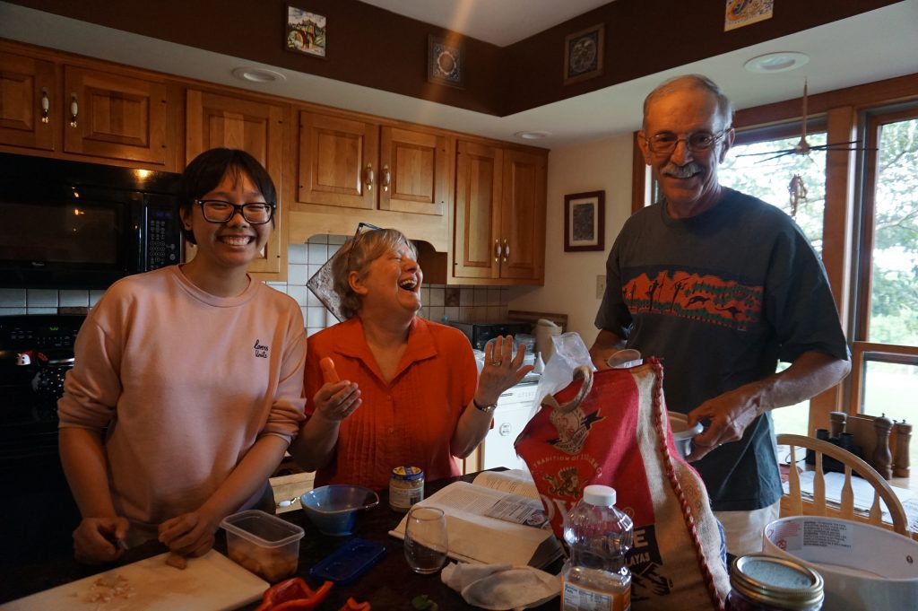 Anh Nguyen stands in a kitchen with Sharon Kalbarczyk and her husband Sam Zigler