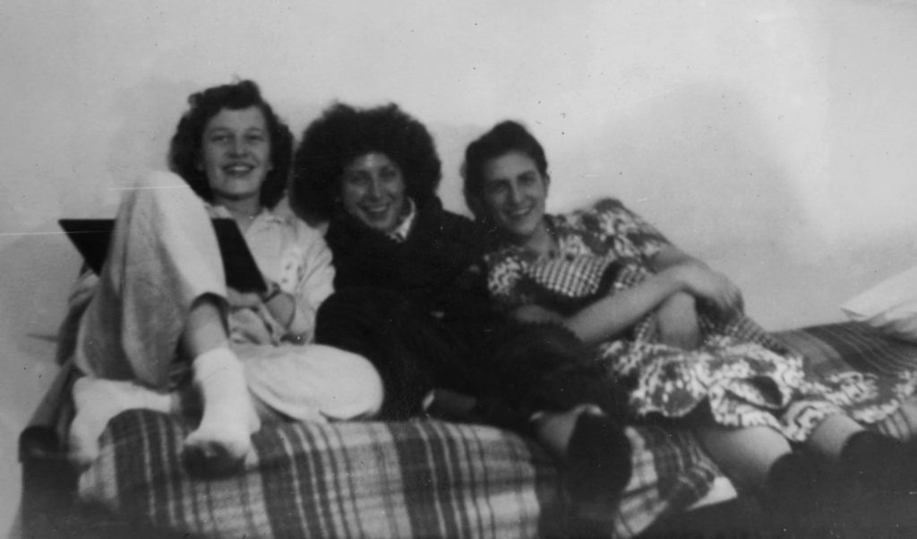 Three women sit together on a couch