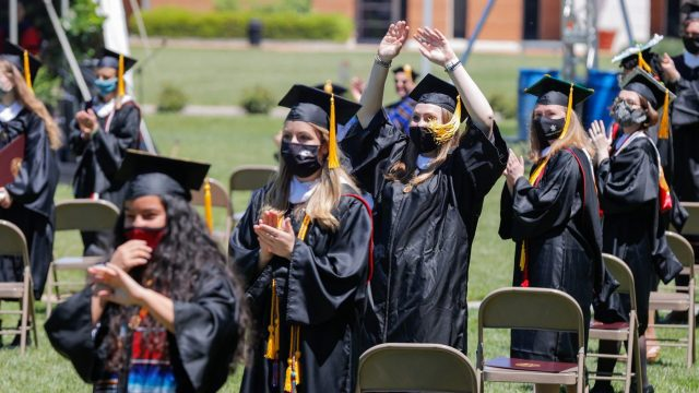 Students wearing graduation robes stand by their chairs and clap.