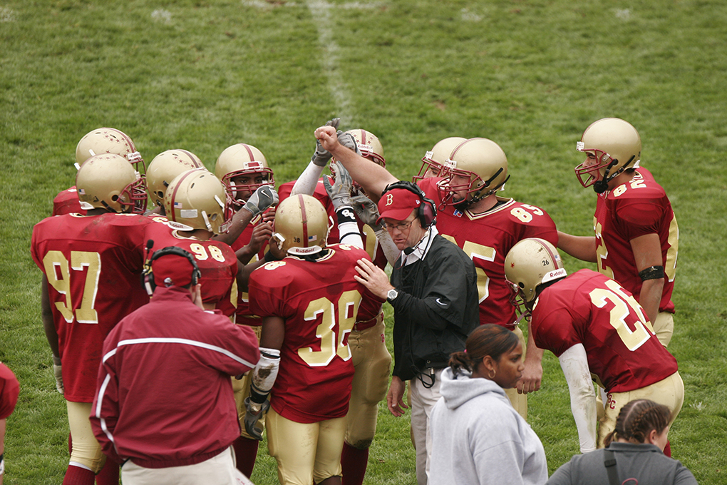 group of football players surrounds a coach