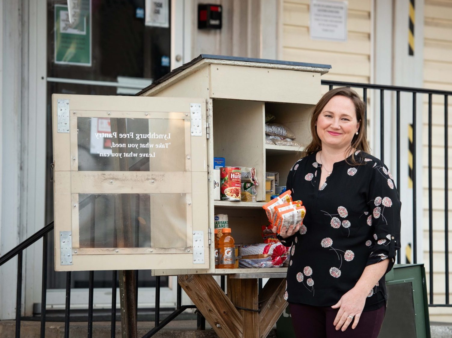 Megan Huffman poses in front of a small community food pantry