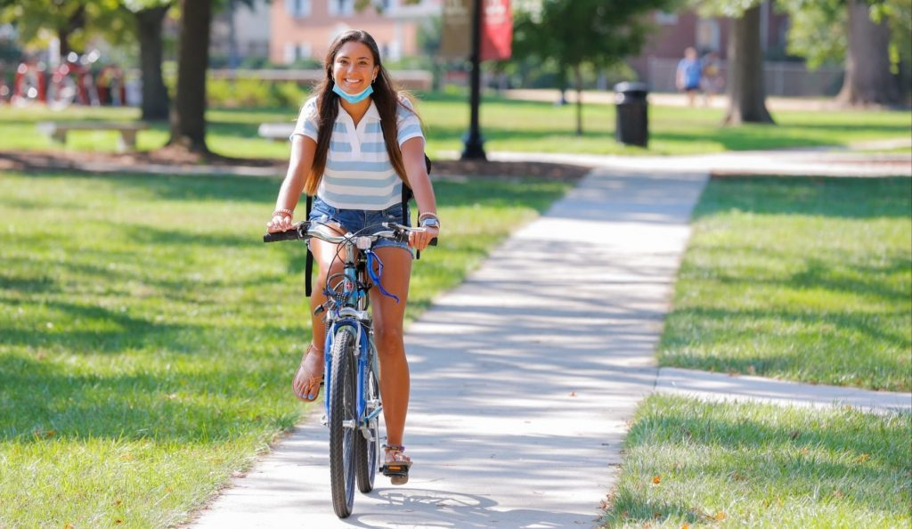 A girl on a bicycle rides through Bridgewater College's campus on the first day of classes 2021