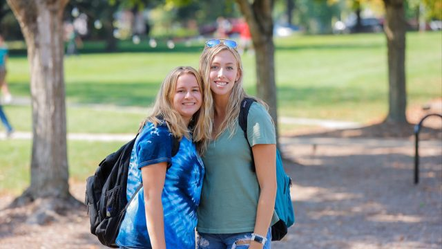 Two girls hug and smile on the first day of classes 2021