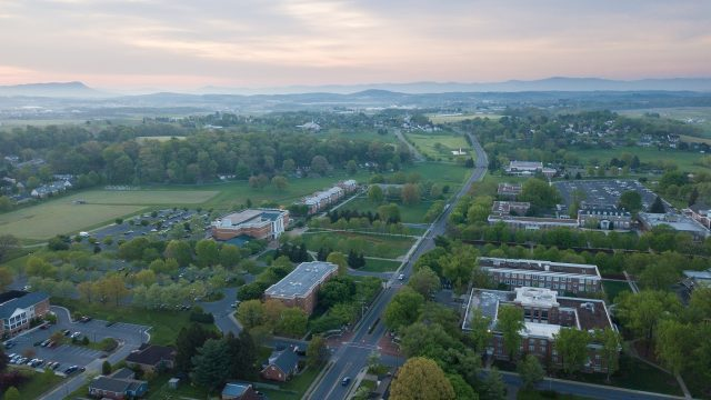 An aerial view of Bridgewater College's campus with the sun rising in the background